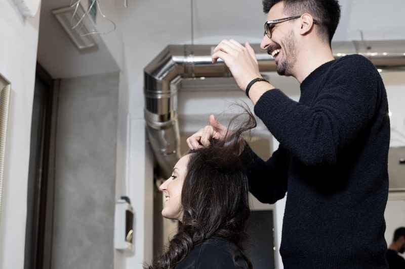 Foto cliente e parrucchiere che sorridono