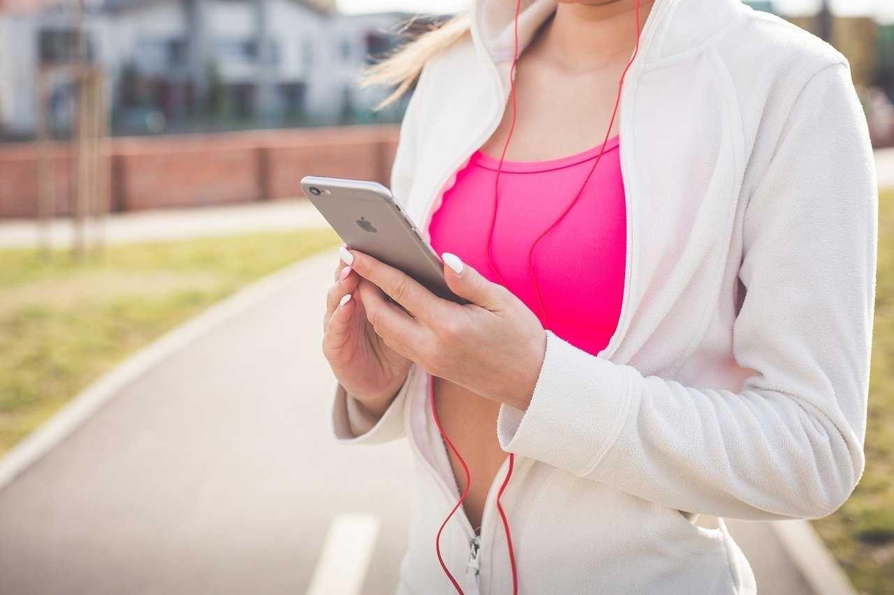 Foto di una donna durante un allenamento con smartohone in mano